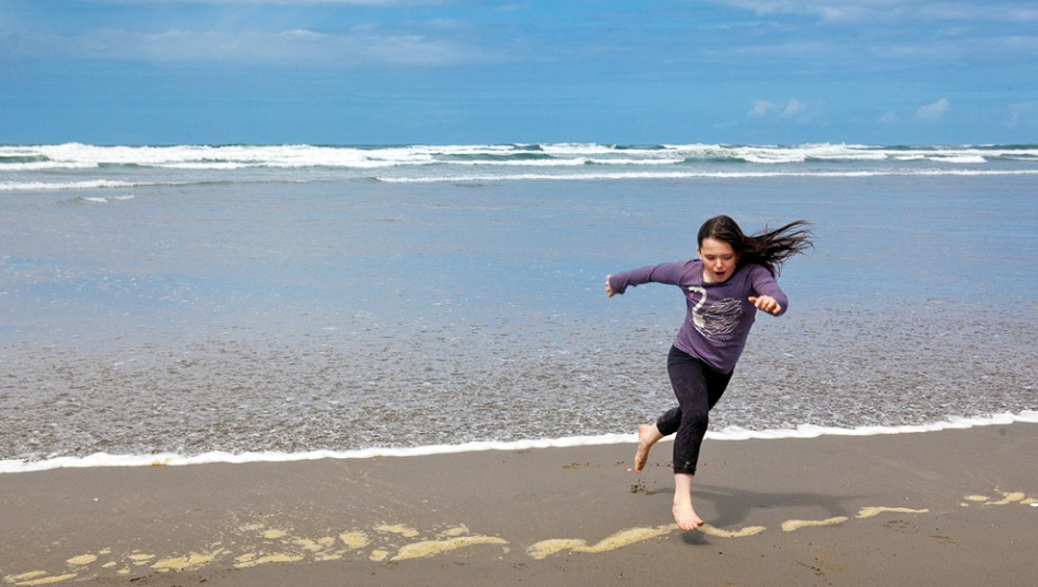 Girl out running the waves as they come the beach