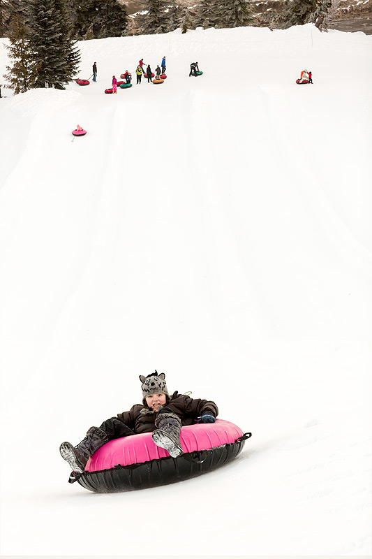 Girl sliding down a mountain in a huge inner tube